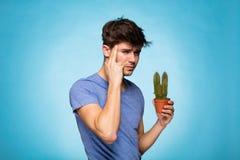 Begrepp med en man som rymmer en kaktus Arkivfoton