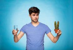 Begrepp med en man som rymmer en kaktus och glace av vatten Royaltyfri Foto