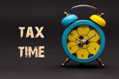 Begrepp ringklocka med skatttiduttrycket som är skriftligt på svart backgr Royaltyfri Fotografi