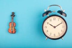 Begrepp, ringklocka och fiol för Tid ledning på blå bakgrund royaltyfri bild