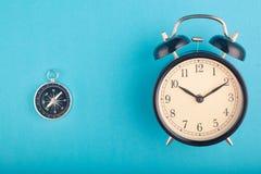 Begrepp, ringklocka och kompass för Tid ledning på blå bakgrund royaltyfri bild