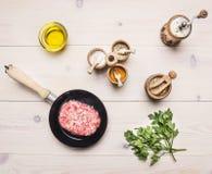 Begrepp som lagar mat den hemlagade hamburgaren med kryddor, smör, ny persilja, rå nötköttliten pastej på en trälantlig backgrou  Royaltyfri Bild