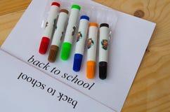 Begrepp tillbaka till skolan Ark av papper med text tillbaka till skolan och färgrika markörer Arkivbild