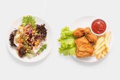 Begreppet av åtlöje upp nya sallad och stekt kyckling- och fransmansmåfiskar ställde in Royaltyfri Bild