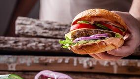 Begreppet av amerikansk kokkonst Hemlagad hamburgare som lagas mat av en man från en bulle, ett meaty nötkött och grisköttkotlett arkivfoto