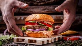 Begreppet av amerikansk kokkonst Hemlagad hamburgare som lagas mat av en man från en bulle, ett meaty nötkött och grisköttkotlett royaltyfria foton