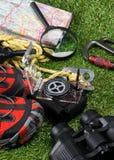 Begreppet av att campa Fotvandra i bergen och turismen, en uppsättning av saker för att fotvandra på en bakgrund av grönt gräs Arkivfoton