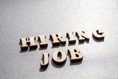 Begreppet av att hyra arbetare som ?r skriftliga, genom ATT HYRA JOBB i tr?bokst?ver p? en gr? bakgrund med den selektiva fokusen royaltyfria foton