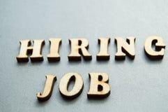 Begreppet av att hyra arbetare som ?r skriftliga, genom ATT HYRA JOBB i tr?bokst?ver p? en gr? bakgrund med den selektiva fokusen arkivbild