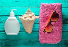Begreppet av att koppla av på stranden Handduk solglasögon, sunblock, skal på turkosen träbakgrund Royaltyfri Fotografi