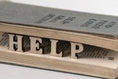 Begreppet av betydelsen av själv-studien av ett utländskt språk Ordet HJÄLP från träbokstäver mellan sidorna av det gammalt arkivbilder