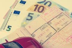 Begreppet av billoppet: passet med gränsstämplarna Några räkning-euro kassa Röd bilmodell Mjukt bearbeta i retro vagel arkivfoto