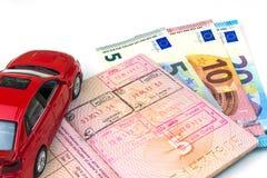 Begreppet av billoppet: passet med gränsstämplarna Några räkning-euro kassa Röd bilmodell På vitbakgrund arkivfoto