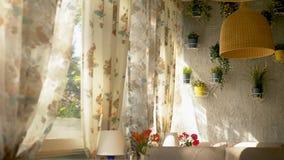 Begreppet av de inre f?nstren stora hell?nga f?nster som dekoreras med gardiner f?r blom- tryck och husv?ggen arkivbilder