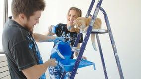 Begreppet av den nya fastigheten Unga par med kattmålning och renovering ett rum i deras nya hus stock video