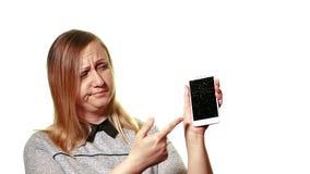 Begreppet av en bruten grej Den frustrerade kvinnan visar att fingret på på den brutna skärmen var aktiveringssmartphonen stock video