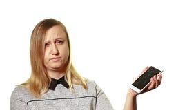 Begreppet av en bruten grej Den frustrerade kvinnan visar hennes hand på den brutna skärmen av smartphonen lager videofilmer