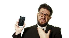 Begreppet av en bruten grej Den uppsökte affärsmannen med exponeringsglas visar en bruten skärmsmartphone, honom förlöjligas lager videofilmer