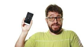 Begreppet av en bruten grej En skäggig man visar smartphonen med en bruten skärm Han förbannar i förtvivlan och är lager videofilmer