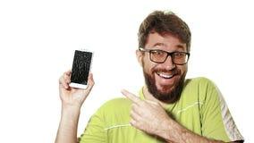 Begreppet av en bruten grej En skäggig man visar smartphonen med en bruten skärm Han skrattar hysterically arkivfilmer