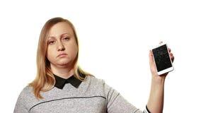 Begreppet av en bruten grej Trött sömnig kvinna som rymmer en smartphone med en bruten skärm lager videofilmer