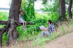 Begreppet av en familjsemester: fadern läser en interestin Arkivfoto
