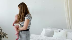 Begreppet av en modern ung familj i en vit lägenhet Mamman sätter behandla som ett barn för att bädda ned att sjunga honom en vag lager videofilmer