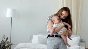 Begreppet av en modern ung familj i en vit lägenhet Mamman sätter behandla som ett barn för att bädda ned att sjunga honom en vag stock video
