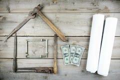 Begreppet av ett hus under konstruktion Gammalt träskrivbord Gamla rostiga snickerihjälpmedel Arkivfoto