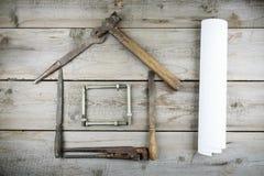 Begreppet av ett hus under konstruktion Gammalt träskrivbord Gamla rostiga snickerihjälpmedel Arkivbilder