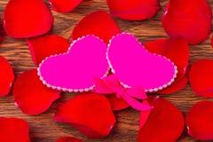 Begreppet av förälskelse och romans: två rosa hjärtor och kronblad av r fotografering för bildbyråer