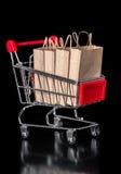 Begreppet av försäljningsshoppingvagnen med pappers- påsar isoleras på bla Arkivbild