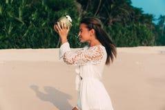 Begreppet av förväntan, verklighet En ung flicka önskade att dricka beautifully bevattnar från kokosnöten, men löjligt arkivfoton