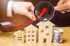 Begreppet av fastighetmarknadstillväxt Förhöjningen i huspriser Stigande priser för hjälpmedel Ökande intresse in royaltyfri foto