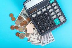 Begreppet av finansiella besparingar som köper ett hus Modellera huset, dollar, mynt och räknemaskinen som isoleras på blå bakgru Royaltyfri Foto