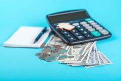 Begreppet av finansiella besparingar som köper ett hus Modellera huset, dollar, mynt och räknemaskinen som isoleras på blå bakgru Royaltyfri Fotografi