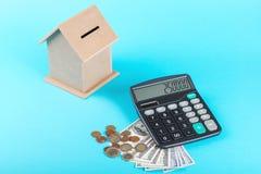 Begreppet av finansiella besparingar som köper ett hus Sparbössa, dollar, mynt och räknemaskin som isoleras på blå bakgrund Royaltyfria Foton