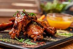 Begreppet av indisk kokkonst Bakade fega vingar och ben i honungsenapsås portiondisk i restaurangen arkivbilder