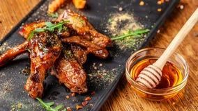 Begreppet av indisk kokkonst Bakade fega vingar och ben i honungsenapsås portiondisk i restaurangen arkivfoton
