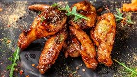 Begreppet av indisk kokkonst Bakade fega vingar och ben i honungsenapsås Portiondisk i restaurangen på en svart arkivbilder