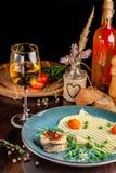 Begreppet av italiensk kokkonst Bakad Seabassfisk med grönsaker och mosade potatisar Ett exponeringsglas av vitt vin på tabellen arkivfoto