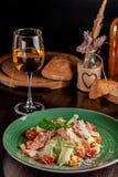 Begreppet av italiensk kokkonst Caesar sallad med laxen, grönsallatblandningen, körsbärsröda tomater och parmesanost glass vit wi royaltyfri foto