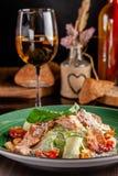 Begreppet av italiensk kokkonst Caesar sallad med laxen, grönsallatblandningen, körsbärsröda tomater och parmesanost glass vit wi royaltyfri fotografi