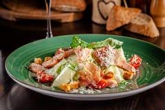 Begreppet av italiensk kokkonst Caesar sallad med laxen, grönsallatblandningen, körsbärsröda tomater och parmesanost glass vit wi arkivfoto