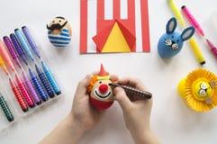 Begreppet av påsken med gulliga och gladlynta handgjorda ägg, en kanin, en clown, en strongman och ett lejon Arkivfoton