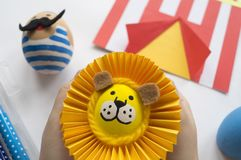 Begreppet av påsken med gulliga och gladlynta handgjorda ägg, en kanin, en clown, en strongman och ett lejon Royaltyfri Bild