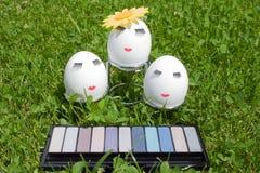 Begreppet av påsken som målar ägg, smink på grönt gräs Royaltyfri Fotografi