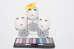 Begreppet av påsken som målar ägg, smink på vit bakgrund Royaltyfri Fotografi