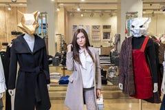 Begreppet av shopping och mode Härlig allvarlig ung brunettflicka i ett klädlager nära skyltdockor med djura maskeringar arkivbild