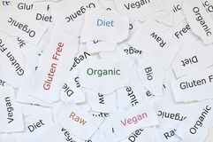 Begreppet av slumpmässiga små stycken av brutet papper som skrivs ut med organiska ord, bantar, fri gluten, rått, bio, strikt veg royaltyfri fotografi